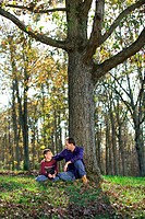 A father and son talking while sitting outdoors at the base of a tree