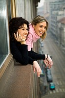 Portrait of two women smiling as they lean out of a window over a street in Milan, Italy