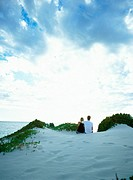Couple on sand dune looking out to sea, rear view