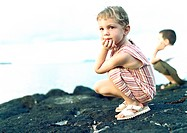 Two children crouching on rock