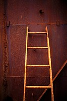 Ladder leaning on metal wall