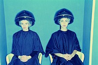 Two women wearing smocks and clear plastic caps sitting underneath hooded dryers