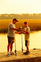 adult male and teenage boy standing on a dock in the marsh baiting their fishing poles