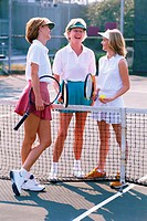 three women talking and holding tennis rackets at the net