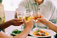 Two couples clinking wine glasses together in the center of a table