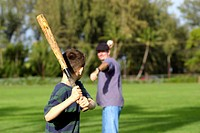 Rear view of boy with baseball bat waiting for father or coach to pitch the ball