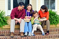 Family sitting on steps of porch while their daughters dig into their Easter baskets
