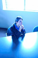 Sad businesswoman sitting at conference table alone with her chin resting in her hands