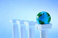 Tops of four columns in a row with a miniature globe resting on the top of one column