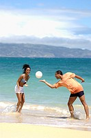 Couple on vacation at the beach playing volleyball in the ocean surf