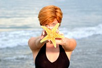 Woman holding a starfish in front of her