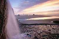 Fall creek tumbles over a waterfall onto the beach at sunset. Hug Point State Recreation Site. Clatsop County. Oregon. USA