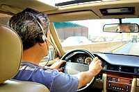 Back view of a man driving and talking on his cell phone using a hands-free headset