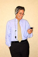 A businessman wearing a headset while looking at his cell phone