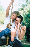couple on a tire swing with cell phone