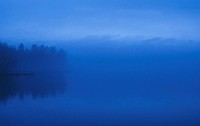 A calm lake and forest in fog, Finland