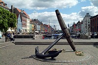 A huge anchor on a square, harbour, boats and houses in background