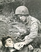 A soldier gives a drink to a wounded man