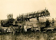 Group portrait of many soldiers sitting on the long barrel of a cannon