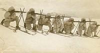 Soldiers wearing skis firing rifles across snowy field