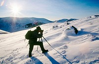 Cairngorms National Park in winter. Walker crossing Cairn Lochan in snow. Highlands. Scotland. UK