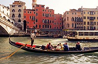 Gondola with tourists on the Grand Canal next to the Rialto Bridge. Venice, Italy