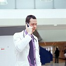 Hospital doctor talking on his mobile phone while he walks down a corridor.