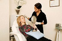Cosmetic treatment. Female patient examining the results of her cosmetic treatment in a mirror, while a clinician applies antiseptic cream to minimise...