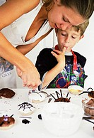 Making cakes. Image 6 of 8. 17- year-old girl helping her 5-year-old brother to decorate fairy cakes for Hallowe´en. For a sequence showing this proce...