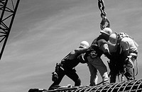 Ironworkers attaching load to crane. I-880 Cypress Project. Oakland, California. USA