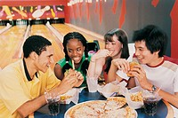 Teenage Boys and Girls Eating Fast Food at a Table in a Bowling Alley