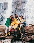 Family of Four Sitting on a Tree Trunk in Front of a Waterfall