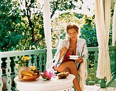 Portrait of a Young Woman Eating Breakfast on the Balcony of Her Home