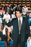 Sports Coach Motivating His Team From the Stands in a Basketball Court