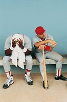 Baseball Players Sit Side by Side on the Bench Defeated