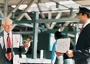 Chauffeur Holding Placard Greets Elderly Businessman at Airport