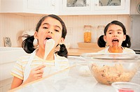 Twin Girls in a Kitchen Licking Spoons