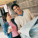 Smiling Couple Standing in Their Home With a Blueprint