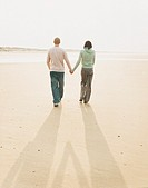 Rear View of a Couple Walking Hand-in-Hand on a Beach