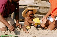 Black family on the beach with young boy building sandcastle.