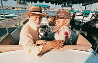 Senior Couple Sitting at the Helm of a Motorboat Moored in a Marina