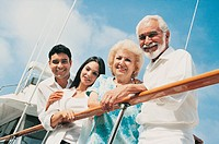 Smiling Family of Four Standing on Deck by the Railing of a Motorboat