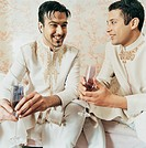 Two Brothers in Traditional Indian Dress Sit Side-by-Side Holding Wine Glasses