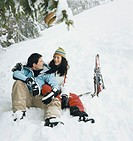 Couple Sitting in Snow on a Ski Holiday
