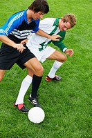 Two soccer players running after ball