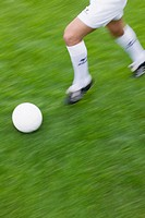 Legs of soccer player running after ball