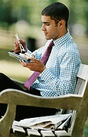 Business Man Eating Sushi On A Park Bench
