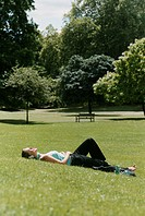 Woman Lying on Grass in a Park Wearing Headphones