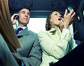 A Businessman With a Mobile Phone Sitting Next to a Businesswoman in the Backseat of a Taxi While She Applys Lipstick