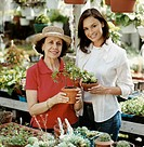 Mother and Daughter Stand Side by Side Holding Potted Plants in a Gardening Centre